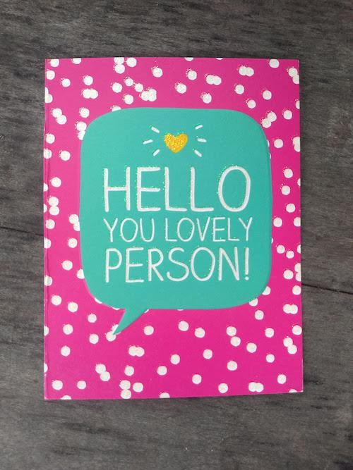 """Image of a card on a blue woodgrain background. Card is pink with a turquoise speech bubble in the middle that says, """"Hello you lovely person!"""" Also in the speech bubble is a yellow heart."""