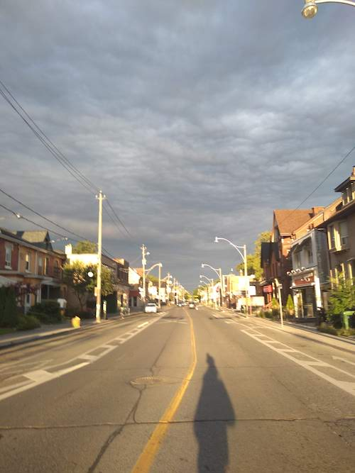 Image of a street in the sunlight against a cloudy, moody sky. The street is empty mostly, and stretched to the horizon. The shadow of the photographer stretches long in the bottom of the shot.