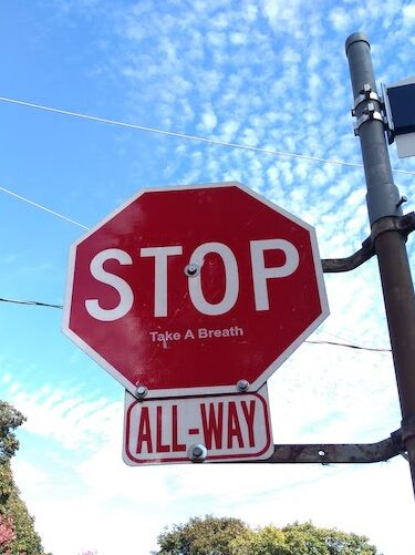 """Photo of a STOP sign against a blue sky with some scattered clouds. Underneath the STOP, someone has pasted a stick that says """"Take A Breath"""""""